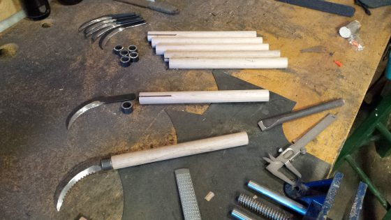 The assembly process for each kama: blade, steel ferrule, wooden handle and a steel pin.